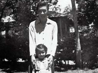 Moriso Teraoka and an unidentified young girl in yard of Wainaku home before he was inducted in the Army. Hilo, Hawaii. March 1943.