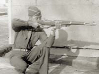 Moriso Teraoka posing with rifle in front of living quarters. Camp Shelby, Mississippi. February 1944.