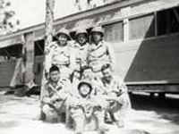 Group of soldiers posing in front of living quarters. Camp Shelby, Mississippi. May 1944.