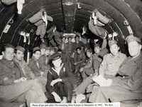 Unidentified soldiers and Moriso Teraoka (second from right) on a DC-3 transport plane flying from the East to the West coast en route home at the end of the war. December 1945.
